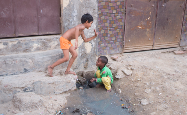 Kids playing in an open sewer.